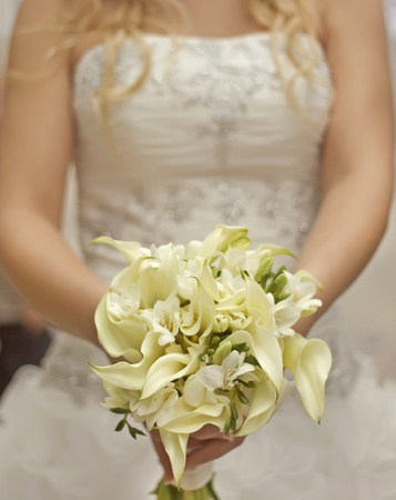 Bride in a white dress with a wedding bouquet of white flowers photo