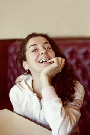 Portrait of young woman with brackets in cafe photo