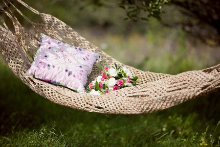pink and white wedding bouquet of roses in a hammock photo