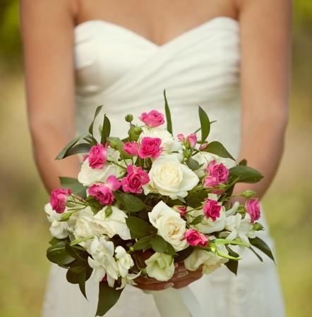 bridal dress: bouquet da sposa rosa e bianco delle rose nelle mani della sposa Archivio Fotografico