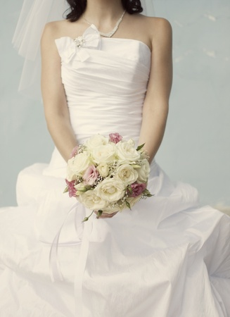 pink and white wedding bouquet of roses in the hands of the bride photo