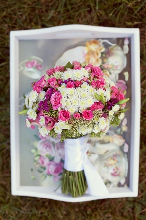 pink and white wedding bouquet in delicate tones on the grass photo