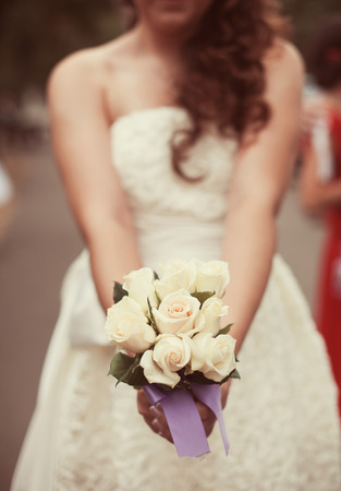 wedding ceremony: Bride in a white dress in summer green park with a bouquet in hand