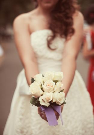 cérémonie mariage: Mariée dans une robe blanche dans le parc d'été vert avec un bouquet à la main