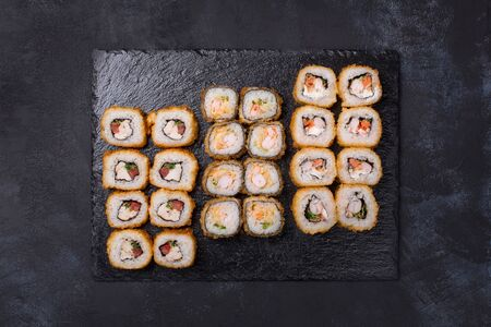 Sushi set with various kinds of hot rolls on a black background. Tempura. Japanese food. Above view