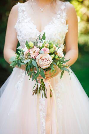Bridal bouquet. Beautiful wedding dress. Close up. Vertical photo.