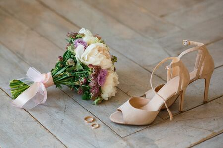 Wedding. Decor. Bride's shoes, a beautiful wedding bouquet, rings, boutonniere are beautifully laid out on a wooden background. Top view. Shadows. Sunlight. Stock fotó