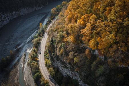 Autumn trees and mountain river and mountain road winding.