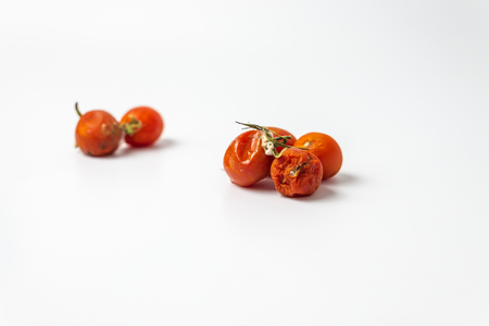 ugly cherry tomato with mold on white background