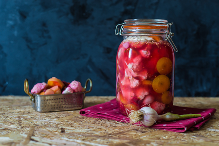 Jar of pickled vegetables by Indian traditional  recipe on wooden background with copy space