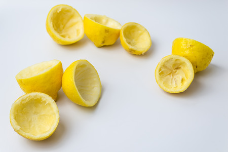 Squeezed lemon peels after making a fresh juice on white background