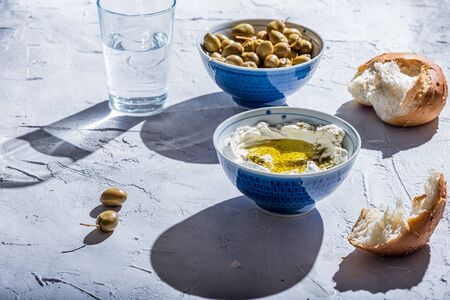 homemade labneh (labaneh) middle eastern soft white goats milk cheese served with zaatar or hyssop and Lebanon green olives , selective focus , hard light effect Stock Photo