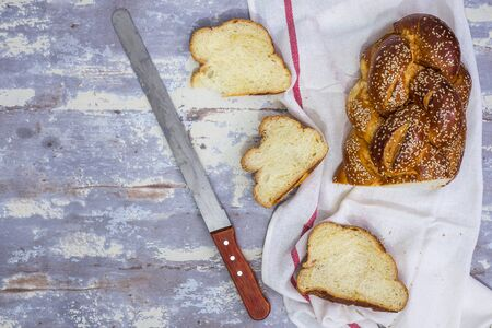 Challah Bread for Shabbat  sliced with knife for bread,  top view  , flat lay with copy space