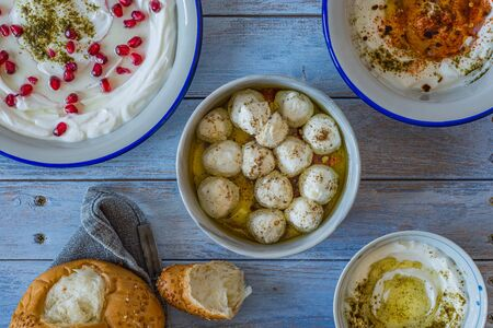 Popular middle eastern appetiser labneh or labaneh, soft white goat milk cheese with bread,4 different kinds of serving, hyssop, red paprika, pomegranate, labneh balls, over rustic table, top view