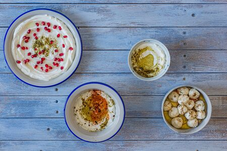 Popular middle eastern appetiser labneh or labaneh, soft white goat milk cheese with, 4 different kinds of serving, hyssop, red paprika, pomegranate, labneh balls, over rustic table, top view