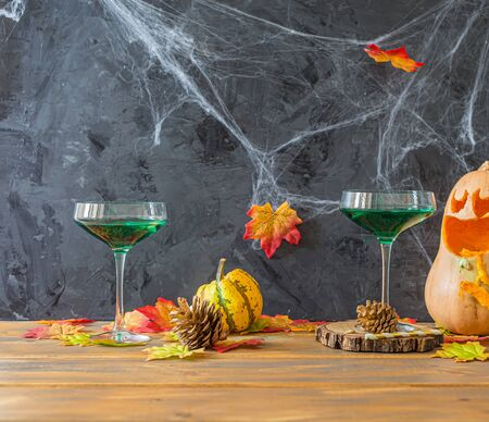 Halloween party with green cocktails and squash with funny face and 2 little pumpkins , side view with copy space