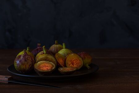 Fresh figs. Dark photo of a figs in black plate on wooden rustic surface, front view. Copy space. Food Photography