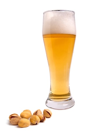 beerglass: light beer with the foam in a tall glass and pistachios isolated on white