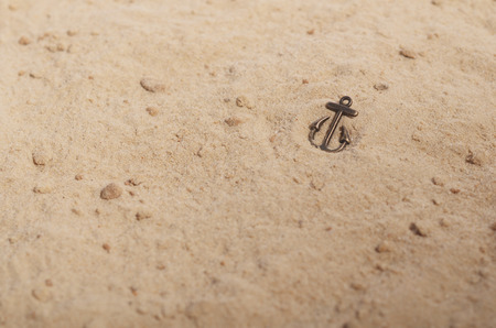 shallow: Bronze anchor on the yellow sand. Shallow depth of field.