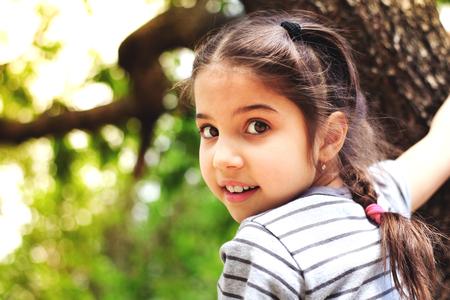 緑の葉と暗い地殻で木の近くで外で遊ぶ若いかわいい女の子。