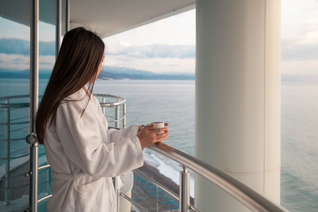 Close up view of beautiful woman luxury relaxing with cup of coffee tea in the hands on blue sky sea on the hotel balkony. Holiday and relaxation concept.