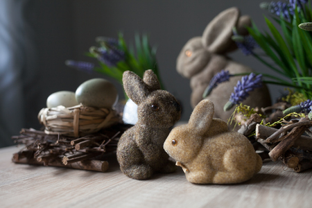 Couple Easter bunny toys and color eggs on the spring background. Rabbits family. Happy Easter holiday concept.