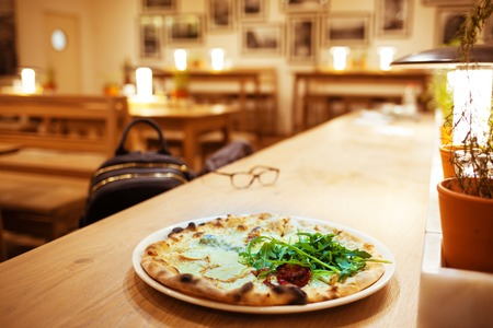 Pizza on the wooden table in the cafe. Interior blurred background. Selective focus.