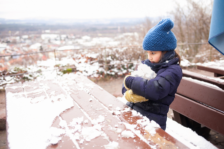 Beautiful young girl in the violet clothes playing with snow outdoor. Awesome view on the town. Stok Fotoğraf