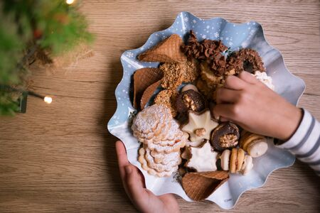 Christmas biscuits in the plate. Child hold a treat in hands. Happy New Year concept.