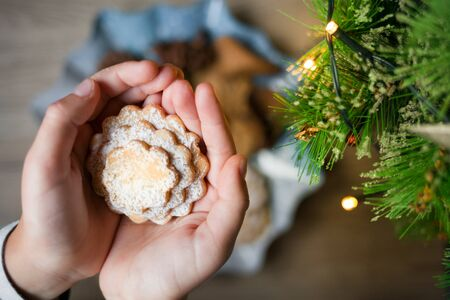 Christmas biscuits in the shape of heart in childrens palms. Happy New Year concept. 写真素材