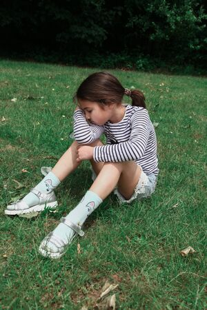 Feeling tired and depressed, upset, sad alone small girl relax on green grass. Parks and outdoor. Foto de archivo