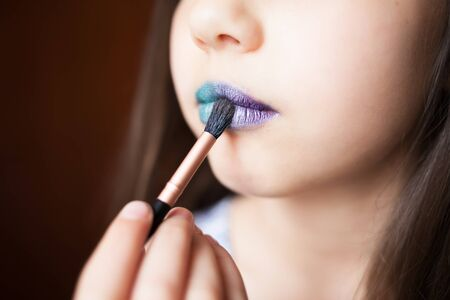 Girl with blue lipsteak on her lips. Glamur modern visage with trendy glowing make-up, colorful make up. Archivio Fotografico