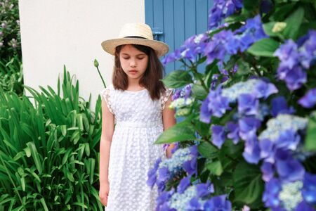 Young girl in white dress stay near old cottage with blue colour door. Bright Hydrangea with blurred blue flowers. Banque d'images