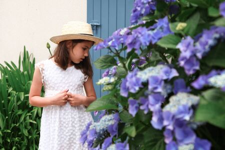 Young girl in white dress stay near old cottage with blue colour door. Bright Hydrangea with blurred blue flowers.