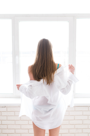 Young pretty girl with long brown hair unclothing a white mens shirt near the window