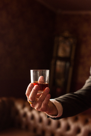 Groom holds in his hand a glass of whiskey indoors