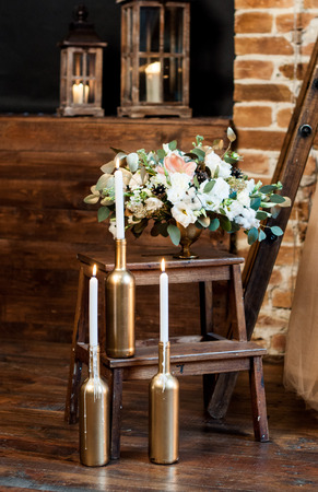 Bridal morning: burning candles on bottles-candlesticks and an arrangement with a fresh flowers in a vase.