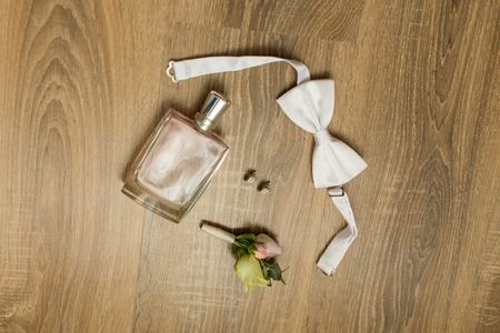 Wedding accessories. Pink perfume, bridal earrings with diamonds, white bowtie and boutonniere with small roses and a wooden background Banque d'images