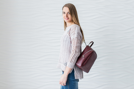 Caucasian beautiful girl with long brown hair in grey pullover with backpack of marsala color. Cheerful studio portret