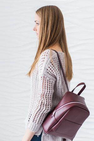 packsack: Caucasian beautiful girl with long brown hair in grey pullover with backpack of marsala color.