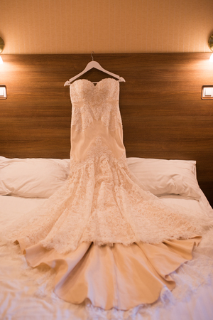 Elegant wedding dress on the bed in the hotel room Stock Photo