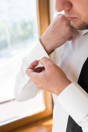 The man adjusts his sleeve on the white shirt. Stock Photo