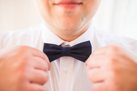 Cute stylish groom in a white shirt, blue necktie. The preparations of the groom. Groom straightens his necktie.