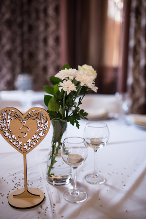 Wedding decoration: candles in glasses, white flowers in vase. Wedding wooden table in a shape of a heart.