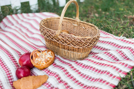 Romantic picnic in the garden - a basket with bakery and apples. Picnic on the lawn. Objects for picnic on a coverlet. Weekend. Stock Photo