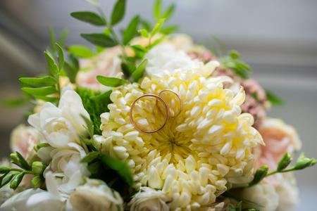 Gold wedding rings lie in a bud of yellow chrysanthemum. Wedding rings lie on a flower bud
