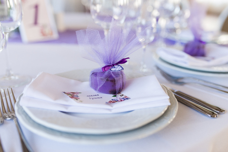 A wedding purple bonbonniere in a shape of heart lying on a white plate Archivio Fotografico