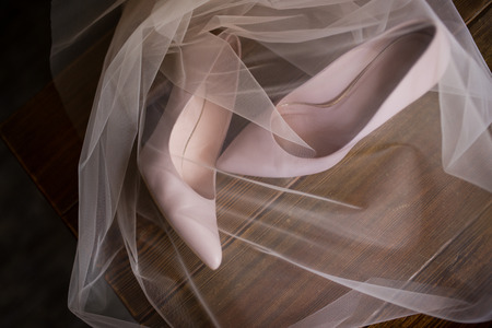 Beige bridal shoes are veiled. Wedding accessories.