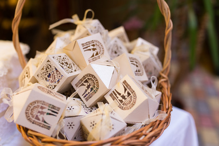 White boxes for guest attending the wedding in the basket. Shaped favors the house that contain confetti. Bonbonniere for guests.