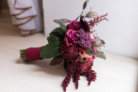 Delicate, expensive, trendy bridal wedding bouquet of flowers in marsala and red color. Wedding accessories. Stock Photo